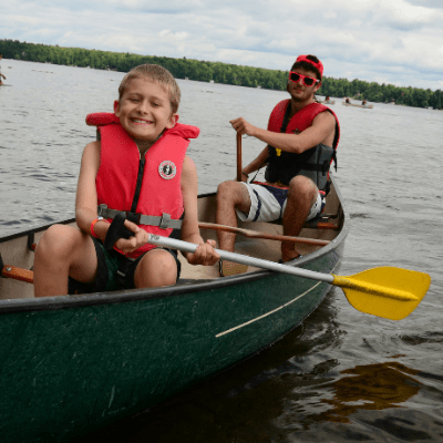 Camper and Counsellor paddling a canoe