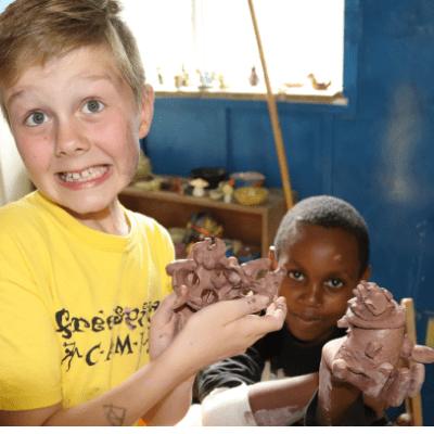 Boys with ADHD and autism showing off the pottery they made