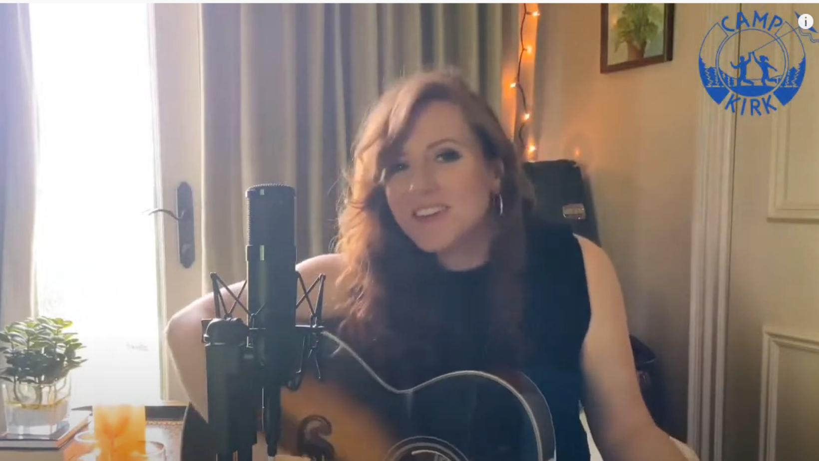 Singer Molly Brown is smiling and plays her guitar. She is sitting in front of a microphone. There is a table to her right with a small house plant, and a drink.